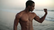 Young black man, the well-trained muscular athlete, make body building exercise on the beach at sunset in Santa Monica, Los Angeles, California, USA