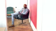 Young black man walks into room and sits in office chair