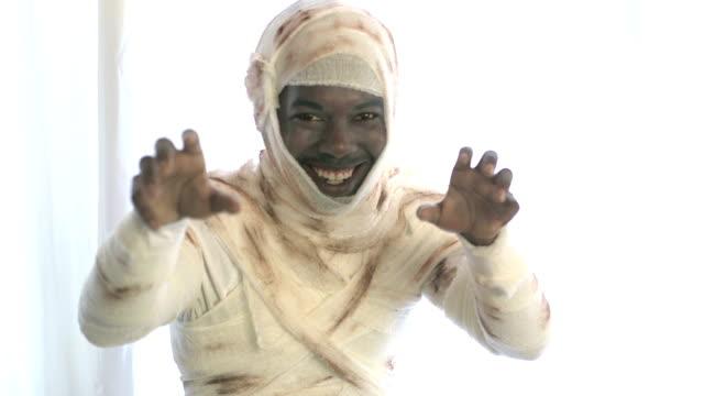 Young black man wearing mummy costume