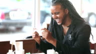 Young black man with dreadlocks laughing at mobile phone