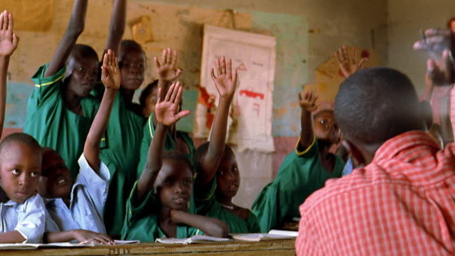 MS young Black schoolchildren sitting at desks + excitedly raising hands / Kenya