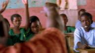 MS PAN young Black schoolchildren sitting at desks + excitedly raising hands / Kenya