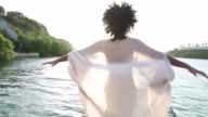 MS Young black woman on wooden boat dock, she looks over her shoulder, smiles then walks along holding her arms out in the breeze.