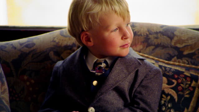 MS PAN PORTRAIT young blonde boy in suit sitting on sofa looking to side + then to camera smiling