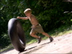 CANTED young blonde boy rolling large inner tube on dirt road in forest