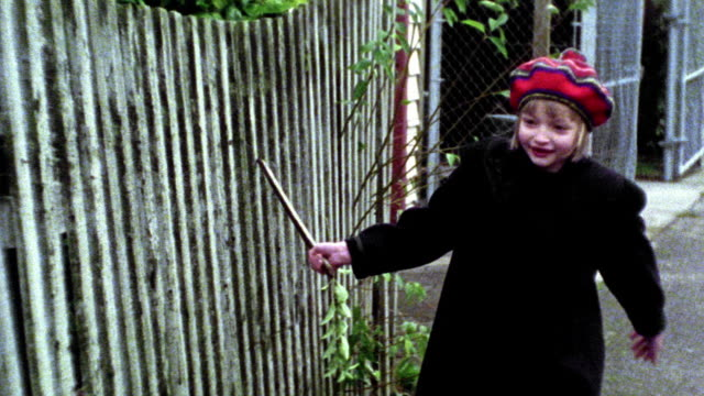 MS young blonde girl in red hat running toward camera next to fence dragging stick along it