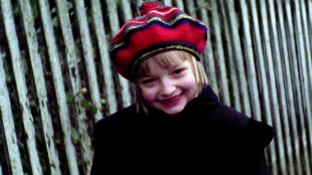 MS PORTRAIT young blonde girl in red hat smiling at camera / fence in background
