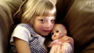 SHAKY MS PORTRAIT young blonde girl lying on sofa cuddling + kissing baby doll
