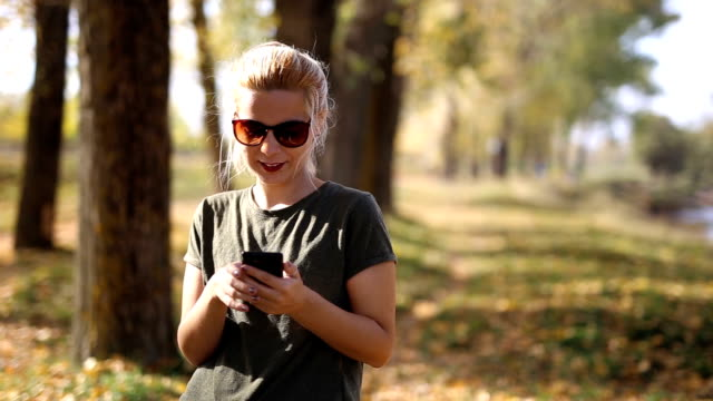 Young blonde in autumn park using smartphone