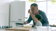Young boy and his grandfather cooking together