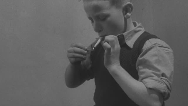 1947 MONTAGE A young boy being caught smoking a cigarette / United Kingdom