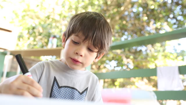 A young boy coloring in a book outdoors on a porch.