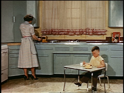 1952 young boy eating at small table in kitchen while woman works at counter