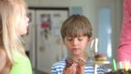 Young Boy Enjoying Cupcake At Birthday Party