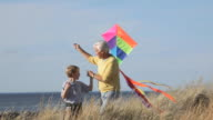 MS TS Young Boy Flying Kite, Walking with Grandfather on Beach Dunes / Eastville, Virginia, USA