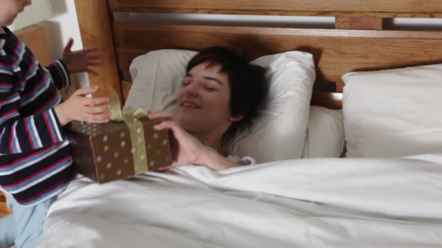 young boy gives mum a present in bed and helps her to open it/UK