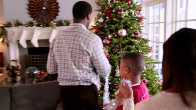 Young boy helps mom and dad string tinsel on Christmas tree