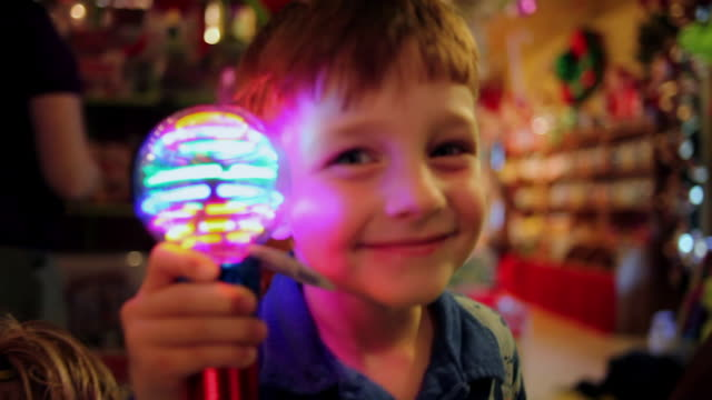 Young boy holds up spinning light to camera smiling in novelty shop