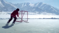 Young boy in a red sweater dribbles a hockey puck a few times back and forth across an outdoor ice rink surrounded by snow capped mountains.