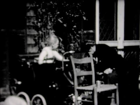 1932 young boy in carriage wearing safety harness