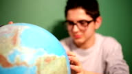 Young boy in classroom looking at globe