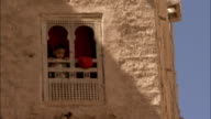 A young boy looks out of a decorative window of a mud brick apartment building.