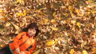 A young boy lying on his back outside with leaves surrounding him