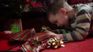 CU young boy peeks into gift box under christmas tree and shows suprise/UK