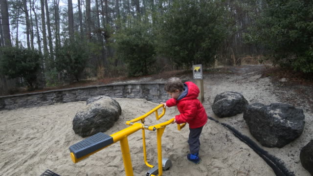 Ung pojke spelar i en lerig sandlåda