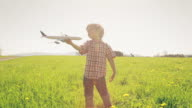 A young boy playing with an airplane in a grass field