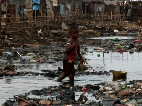 Young boy playing with paper boat in extremely polluted river, Kroo Bay, Sierra Leone, West Africa
