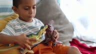 CU Young boy playing with toy dinosaurs.