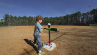 Young boy practicing batting on an empty baseball field