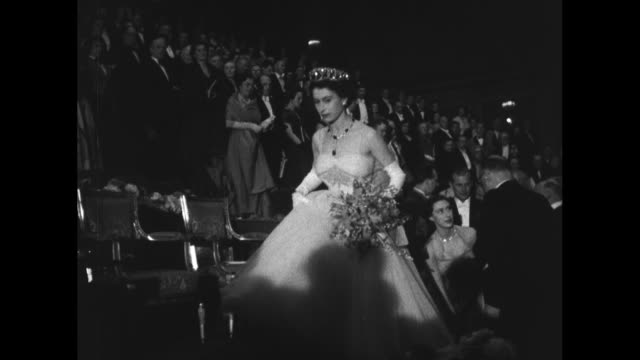 MS young boy presents Queen Elizabeth II with a bouquet and bows as she accepts it / Queen carries bouquet as she walks to her seat followed by...