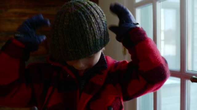 MS CU Young boy putting on snow cap / Stowe, Vermont, United States