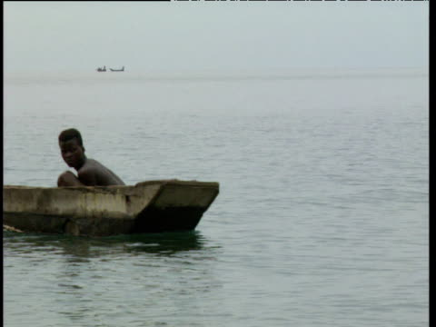 Young boy rows paddle boat across river Democratic Republic of Congo