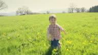 A young boy running in a green grass field