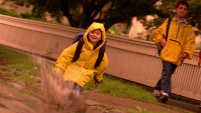 ORANGE CANTED PAN young boy running + jumping in puddle with older boy + girl watching