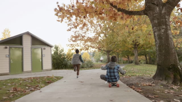 Young Boy Running Next to His Brother as He Rides an Electric Skateboard