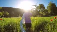 Young Boy Runs through Field Flying Airplane