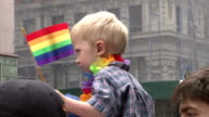 A young boy sits on top of his fathers shoulders and waves a rainbow flag at the annual Gay Pride Parade in New York City