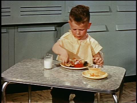 1952 young boy sitting at small table eating lunch in kitchen