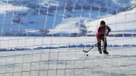 Young boy skating towards a hockey net; about to make a goal.