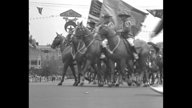 Young boy stands in front of crowd facing street waves his arms as if conducting a band / Shriners' color guard moves past on horseback these are...