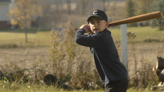 MS SLO MO Young boy swinging and missing baseball / Chelsea, Michigan, United States