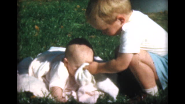 1957 young boy wipes face of sister with blanket