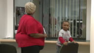 Young boy with mother holding paperwork at counter in job center/ Antioch California USA/ AUDIO