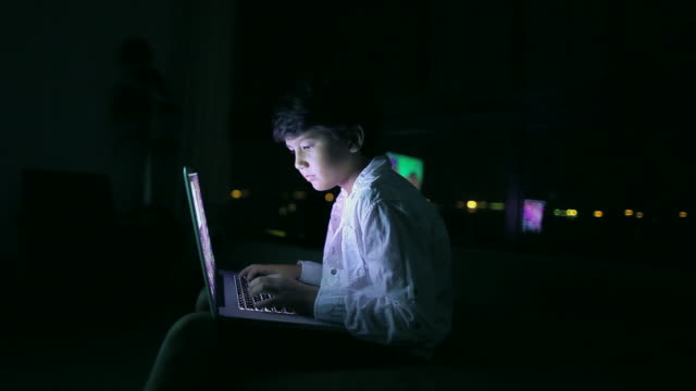 MS Young boy working on laptop computer at night/Singapore