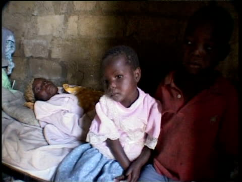 Young boys at bedside of sick mother, Zambian hospice, S. Africa
