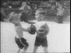 Young boys in boxing gear are weighed on a scale by coach Spike Webb / mothers assist the young boys / little girl kisses a young boxer / young...